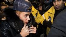 Canadian musician Justin Bieber is swarmed by media and police officers as he turns himself in to city police on Jan. 29, 2014. (NATHAN DENETTE/THE CANADIAN PRESS)