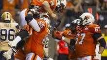 BC Lions tackle Ben Archibald lifts QB Travis Lulay while celebrating Lulay's touchdown (ANDY CLARK/REUTERS)