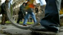 Pedestrians walk and ride bicycles past Rome's ancient Colosseum, February 8, 2004. (ALESSIA PIERDOMENICO/REUTERS)