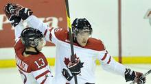 Team Canada forward Mark Stone, right, celebrates his goal with teammate Freddie Hamilton, left, while playing against Team Switzerland during first period exhibition hockey action in preparation for the upcoming IIHF World Junior Championships in Red Deer, Alta., on Thursday, Dec. 22, 2011. (Nathan Denette/THE CANADIAN PRESS)