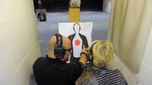 Firearms instructor Mike Magowan (L) works with student Debra Dunbar during a concealed weapons permit class at Take Aim Gun Range in Sarasota, Florida December 15, 2012. (BRIAN BLANCO/REUTERS)