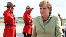 Mounties salute German Chancellor Angela Merkel as she arrives at the Canada Reception Centre in Ottawa, Wednesday, August 15, 2012. (Patrick Doyle/CP)