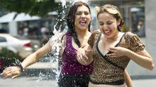 People cool down in the water sprinklers at Dundas Square as they take in the extreme heat in Toronto on Tuesday, June 19, 2012. Environment Canada has issues a heat alert for the next few day in Southern Ontario and Toronto (Nathan Denette/The Canadian Press)