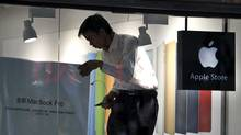 In this photo taken Thursday, July 21, 2011, a Chinese man works on a poster at a shop masquerading as a bona fide Apple store in downtown Kunming in southwest China's Yunnan province. (AP)