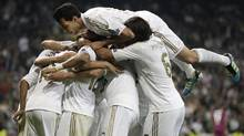 Real Madrid players celebrate a goal by Mesut Ozil against Lyon on Tuesday. (Arturo Rodriguez/Associated Press)