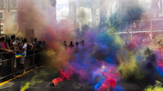 Members of the Black Lives Matter movement stand amidst coloured clouds from smoke grenades at the 2016 Pride Parade in Toronto.