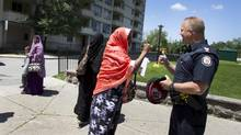 Police have set up an outreach team that will maintain a visible presence in the Toronto neighbourhood in the months to come. (Peter Power/The Globe and Mail)