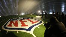 The NFL logo at midfield of MetLife Stadium is illuminated by lights on television reporters' videocameras as members of the media are given a tour under a tarp used by crews to keep the turf dry ahead of Super Bowl XLVIII, Wednesday, Jan. 15, 2014, in East Rutherford, N.J. (Julio Cortez/AP)