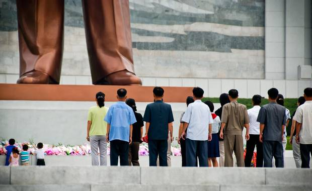 Visitors stand at the base of the Mansudae Grand Monument outside the Korean Revolution Museum.