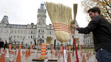 A protester installs brooms on road construction signs while asking for a public inquiry in the Quebec construction industry on Oct. 18, 2011 at the legislature in Quebec City. (Jacques Boissinot/Jacques Boissinot / The Canadian Press)