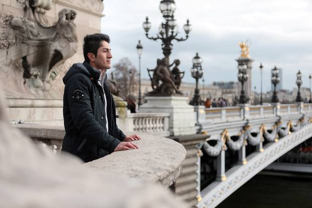 Mikahil looks out onto the Seine River from a bridge in Paris.