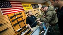 Kenny Brand of Blue Ridge Arsenal, left, assists brothers Tony Drosos, 32, and Peter Drosos, 30, with some of the firearms in Chantilly, VA Tuesday, December 18, 2012. (Kevin Van Paassen/The Globe and Mail)
