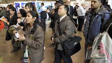 File photo of job seekers checking postings at a jobs fair in Toronto. (J.P. Moczulski for The Globe and Mail)