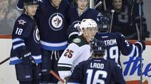 Winnipeg Jets forward Blake Wheeler (26) celebrates his goal against the Minnesota Wild with teammates forward Bryan Little (18) and defenceman Jacob Trouba (8) during the first period at MTS Centre. (Fred Greenslade/USA Today Sports)