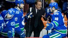 Vancouver Canucks' head coach John Tortorella, centre, gives instructions to Jannik Hansen (36) as Ryan Kesler (17) listens after the Canucks scored the go-ahead goal against the Los Angeles Kings during third period NHL hockey action in Vancouver, B.C., on Saturday April 5, 2014. (DARRYL DYCK/THE CANADIAN PRESS)