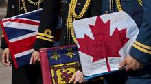 Navy, army and air force officers, left to right, hold flags of the three forces at a ceremony in Halifax on Tuesday, Aug. 16, 2011. (Andrew Vaughan/CP)