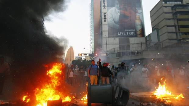 Demonstrators make a barricade of burning garbage during a protest against Venezuela's President Nicolas Maduro's government in Caracas February 12, 2014. A demonstrator was killed during an anti-government rally in Caracas on Wednesday, Reuters witnesses said. A Reuters cameraman and a photographer both heard shots and saw one protester had fallen to the ground. The person was then carried away dead. (Carlos Garcia Rawlins/REUTERS)