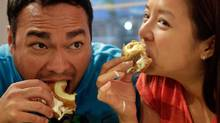 Bryan Yong (left) and Kaycie Luong, from Sacramento, Calif., as they eat their Cronuts, a croissant-donut hybrid, at the Dominique Ansel Bakery, in New York (Richard Drew/AP)