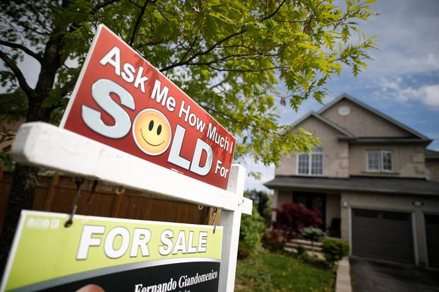 A real estate sign that reads 'For Sale' stands in front of housing in Vaughan, a suburb in Toronto on May 24, 2017.