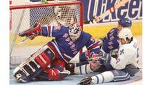 Quebec Nordiques Mike Ricci is dragged down by New York Rangers Adam Graves as he scores past Rangers goalie Mike Richter during first period of game 5 playoff action on May 14, 1995 in Quebec. (Clement Allard/CP)