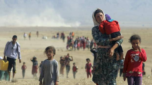 Displaced people from the minority Yazidi sect, fleeing violence from forces loyal to the Islamic State in Sinjar town, walk towards the Syrian border, on the outskirts of Sinjar mountain on Aug. 11, 2014. (RODI SAID/REUTERS)