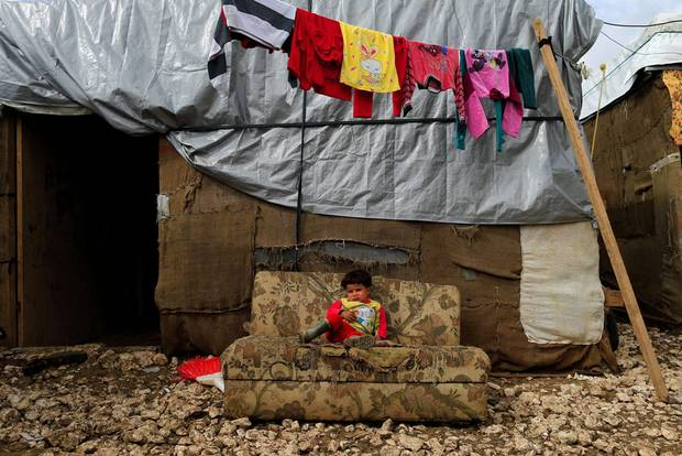 A Syrian refugee child sits on a sofa outside her family's tent at a refugee camp in the town of Hosh Hareem, in the Bekaa valley, east Lebanon, Wednesday, Oct. 28, 2015.