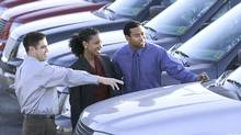 Salesman and couple car shopping. (Ron Chapple/Thinkstock Images)