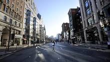 The day after: A woman crosses an empty street near the site of the two explosions on Tuesday, as a large part of downtown Boston remained cordoned off as a crime scene. (GRETCHEN ERTL/NYT)