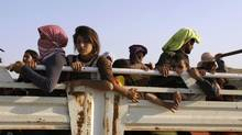 Displaced people from the minority Yazidi sect, fleeing the violence in the Iraqi town of Sinjar, travel in a vehicle as they re-enter Iraq from Syria at the Iraqi-Syrian border crossing in Fishkhabour, Dohuk province, August 14, 2014. (YOUSSEF BOUDLAL/REUTERS)