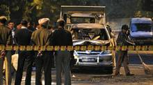 A worker sweeps debris as Indian police officers gather around car belonging to the Israel Embassy, that was damaged in an explosion in New Delhi, India, Monday, Feb. 13, 2012. (Kevin Frayer/AP/Kevin Frayer/AP)