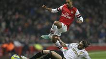 Arsenal's Theo Walcott leaps over the challenge of Swansea City's Chico Flores during their English FA Cup replay soccer match at Arsenal's Emirates stadium in London, Wednesday, Jan. 16, 2013. (Alastair Grant/AP)