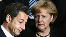 France's President Nicolas Sarkozy and Germany's Chancellor Angela Merkel (R) pose for a family photo during a two-day EU leaders summit in Brussels March 19, 2009. (Francois Lenoir/REUTERS)