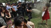 A Turkish riot policeman uses tear gas against a woman as people protest against the destruction of trees in a park brought about by a pedestrian project, in Taksim Square in central Istanbul May 28, 2013. In her red cotton summer dress, necklace and white bag slung over her shoulder she might have been floating across the lawn at a garden party; but before her crouches a masked policeman firing teargas spray that sends her long hair billowing upwards. Endlessly shared on social media and replicated as a cartoon on posters and stickers, the image of the woman in red has become the leitmotif for female protesters during days of violent anti-government demonstrations in Istanbul. (OSMAN ORSAL/REUTERS)