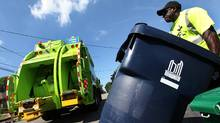An employee of Green For Life waste collection picks up recycling and compost in the neighbourhood of Sheppard Avenue and Dufferin Street in Toronto, August 07, 2012. Starting on Tuesday, waste collection in the area west of Yonge Street to the Humber River was contracted out to GFL. (Deborah Baic/The Globe and Mail)