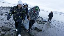 Schoolchildren help hunters returning from a seal hunt at Cape Dorset, Nunavut. (Peter Power/The Globe and Mail)