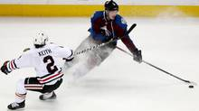 Chicago Blackhawks defenseman Duncan Keith, left, reaches out with his stick to stop Colorado Avalanche center Matt Duchene as he heads down the ice ith the puck in the first period of an NHL hockey game in Denver on Wednesday, March 12, 2014. (Associated Press)