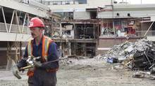 A worker walks by the rubble of the Algo Centre Mall in Elliot Lake, Ont., on June 27. The mayor of Elliot Lake says demolition has begun on the mall where two people died and around 20 were injured when part of its roof collapsed. (Nathan Denette/THE CANADIAN PRESS)