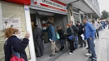 People stand in line to enter a government-run employment office in Madrid in this file photo. (ANDREA COMAS/REUTERS)