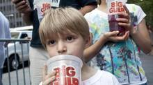 Benjamin Lesczynski, 8, of New York, takes a sip of a Big Gulp while protesting the proposed soda-ban that New York Mayor Michael Bloomberg has suggested, outside City Hall in New York July 9, 2012. Under the proposed law, sugar drinks with no nutritional value would be banned from sale in New York in containers larger than 16 ounces (454 grams). (ANDREW BURTON/REUTERS)