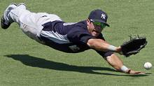 New York Yankees center fielder Austin Krum dives but cannot make the play on a two-RBI triple by Minnesota Twins Matt Tolbert during the second inning of a spring training baseball game in Fort Myers, Fla., Sunday, March 27, 2011. (AP Photo/Charles Krupa) (Charles Krupa)