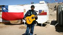 A young man plays guitar at the encampment beside the San Jose mine, near the city of Copiapo, 800 km north of Santiago on October 12, 2010. (HECTOR RETAMAL/AFP/Getty Images)