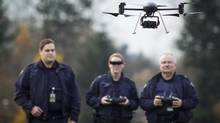 Constable Daron Babor, Corporal Genevieve Dussault and Corporal Paul Vermeulen, members of the RCMP's Integrated Collision Analysis and Reconstruction Service, demonstrate an unmanned aerial vehicle used by the RCMP for collision analysis. (John Lehmann/The Globe and Mail)
