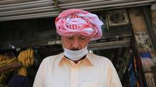 A Muslim pilgrim wears a surgical mask to help prevent infection from a respiratory virus known as the Middle East Respiratory Syndrome (MERS) in the holy city of Mecca, Saudi Arabia on May, 13. (Hasan Jamali/AP)