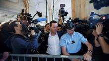 Journalists surround former Societe Generale trader Jerome Kerviel, centremas he follows a gendarme to pass a barrier upon arrival in court for the first day of his trial to appeal his three-year jail term in Paris June 4, 2012. (JULIEN MUGUET/REUTERS)