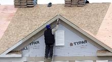 A worker caulks the peak of a new condominium complex under construction in Pepper Pike, Ohio. (Tony Dejak/AP Photo)