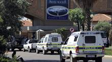 "Police vehicles enter the private townhouse complex where South African ""Blade Runner"" Oscar Pistorius lives in Pretoria February 14, 2013. Pistorius, a double amputee who became one of the biggest names in world athletics, was charged on Thursday with shooting dead his girlfriend, model Reeva Steenkamp, at his upscale home in Pretoria. (STRINGER/Reuters)"