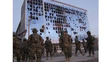 Afghan National Army soldiers stand in front a building damaged during a fierce gun battle in Helmand province, Afghanistan, on Friday. (Abdul Khaliq/AP2010)