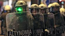 Police in riot gear descend on an anti-austerity protest outside the Greek parliament in Athens on Feb. 19, 2012. (YIORGOS KARAHALIS/REUTERS)