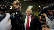 Mayor Rob Ford leaves his office with the help of security officers and his driver as he tries to make his way through the media outside his office in Toronto on November 8, 2013. (DEBORAH BAIC/THE GLOBE AND MAIL)
