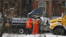 Toronto police officers from the task force collect evidence on Keele Street, south of Dundas where the driver of a stolen snow plow was shoot by police after hitting another officer with the vehicle, Toronto Jan. 12, 2011. (Fernando Morales/The Globe and Mail)